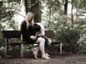 Schwangeres Paar sitzt auf einer Bank