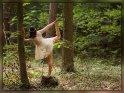 Tänzerin posiert mit hochgestrecktem Bein im weißen Kleid im Wald-