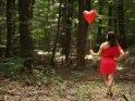 Eine junge Frau im pinken Kleid hält einen Herzluftballon an einer Schnur während sie durch den Wald läuft.