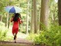 Mädchen im roten Kleid läuft mit einem Regenschirm und einem buten Ball hüpfend einen Waldweg entlang.