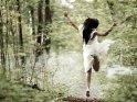 Frau im Brautkleid springt auf einem Waldweg mit leichtem Nebel in die Luft.