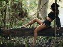 Hexe sitzt auf einem Baumstamm