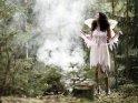 Eine Fee oder Elfe im Wald schaut den aufsteigenden Nebelschwaden hinterher.