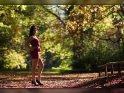 Foto einer Frau im Kleid, die in einem herbstlich bunt gefärbten Park steht.