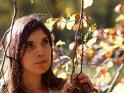 Lustiges Foto einer Frau, die zwischen bunten Herbsblättern steht, während sie eines dieser Blätter im Mund hat.
