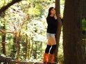 Eine Frau im herbstlichen Outfit steht im Wald und kuschelt sich dabei an einen Baum.