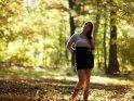 Dieses Foto zeigt eine Frau, die verträumt im herbstlichen Wald steht.