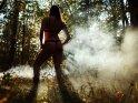 Eine Frau in Dessous steht im nebeligen Herbstwald. Dabei steht sie vor der Sonne und wirft Schatten auf den Nebel, so dass die einzelnen Lichtstrahlen sichtbar zu werden scheinen.