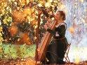 Eine Harfenspielerin spielt in mittelalterlicher Gewandung unter einem herbstlichen Baum auf ihrer Harfe.