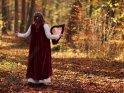 Musikerin steht im mittelalterlichen Gewand mit einer Harfe im herbstlichen Wald.