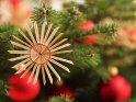 Strohstern an einem Weihnachtsbaum mit roten Kugeln