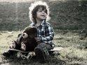 Junge sitzt mit einem Teddybären auf einem Skateboard