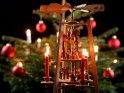 Weihnachtspyramide mit der Darstellung von der Geburt Jesu vor einem Christbaum im Hintergrund.