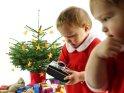 Zwillinge im Weihnachtsoutfit stehen am Weihnachtsbaum mit einem alten Fotoapparat.