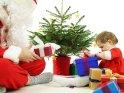 Ein Kleinkind sitzt vor dem Weihnachtsbaum und packt die vom gegenüber sitzenden Weihnachtsmann übergebenen Geschenke aus.