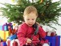 Ein kleines Mädchen sitzt telefonierend unter einem Weihnachtsbaum.
