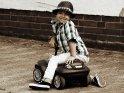 Kleiner Junge auf einem Rutschauto