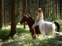 Im weißen Kleid hoch zu Ross im Wald