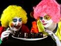 Zwei Clowns machen sich über einne Teller voll Schaumküsse her.