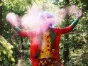Ein Clown wirft Farbpulver in die Luft und erzeugt so für eine Farbwolke vor seinem Kopf.