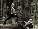 Eine junge Sportlerin dehnt sich im Wald während ihre Freundin ihr dabei zuguckt.