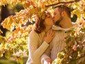 Küssendes Paar unter herbstlich bunten Blättern