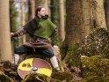 Wikingerin posiert auf einem Felsen im Wald