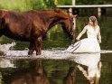 Frau im Hochzeitskleid geht mit einem Pferd in einen See