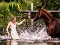 Eine junge Frau im Brautkleid steht mit einem Pferd im See und wird von diesem nassgespritzt.