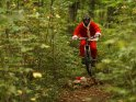 Weihnachtsmann springt mit dem Mountainbike über den Geschenksack
