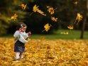 Glückliches Kleinkind im herbstlichen Blätterregen