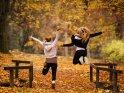 Frauen machen Freudensprünge im Herbstlaub