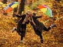 Zwei Freundinnen stehen mit Regenschirm im Herbstlaub und geben sich ein Küsschen