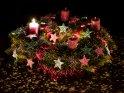 Extrem bunter Adventskranz mit glitzernden Sternen und einer brennenden Kerze für den 1. Advent.