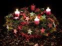Extrem bunter Adventskranz mit glitzernden Sternen und drei brennenden Kerzen für den 3. Advent.