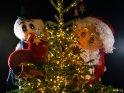 Der Weihnachtsmann versteckt sich mit einem Schneemann hinter einem Weihnachtsbaum.