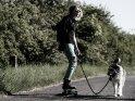 Junge Frau auf einem Lonboard im punkigen Outfit hat ihren Hund an der Leine.