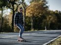 Longboarderin auf einer herbstlichen Straße