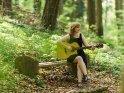 Junge Frau sitzt Gitarre spielend auf einer Bank im Wald.