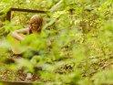 Eine Frau sitzt im Wald und spielt auf einer Gitarre.    Dieses Kartenmotiv ist seit dem 28. April 2018 in der Kategorie Musik.
