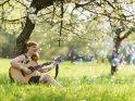 Eine singende Gitarrenspielerin sitzt unter einem Kirschbaum.