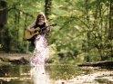 Eine Gitarrespielerin spritzt beim Spielen mit Wasser in Richtung Betrachter.