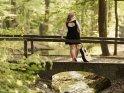 Eine Frau mit Gitarre steht auf einer kleinen Steinbrücke.
