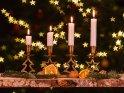 Adventsleuchter mit vier brennenden Kerzen zum vierten Advent.