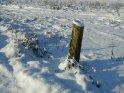 Schneebedeckter Holzpfahl in Mitten einer verschneiten Winterlandschaft